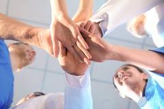 Unga medicinska doktorer som tillsammans sätter händer silhouettes det bl?a begreppsfolket f?r bakgrund skyenhet fotografering för bildbyråer
