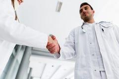Unga medicinska kollegor skakar händer royaltyfria foton
