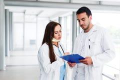 Unga medicinska kollegor som analyserar data på Paperboard royaltyfria bilder