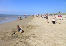 Unga mellan skilda raser lyckliga skämtsamma parinnehavhänder som går på stranden som har gyckel på loppsemestern - kvinnor som l Arkivfoton