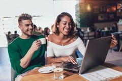 Unga mellan skilda raser par som spenderar tid i hållande ögonen på massmedia för kafé på bärbara datorn royaltyfri fotografi