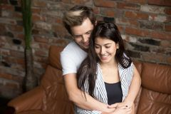 Unga millennial par som hemma omkring omfamnar, lyckligt första pre arkivbild