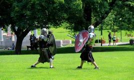 Unga män i den medeltida dräkten som är beträffande - anta strid, parkerar kongressen, Saratoga, 2 Arkivfoton