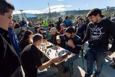 Unga män som spelar schack i folkmassa av spelare av konkurrens på stadsfestivalen Tbilisoba Arkivbild