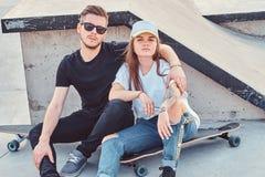 Unga moderiktiga par sitter p? solig skatepark med deras longboards arkivfoton