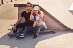 Unga moderiktiga par sitter p? solig skatepark med deras longboards arkivbild