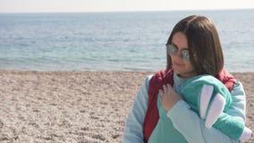Unga moderlugnar hennes son på stranden på en solig vårdag lager videofilmer