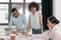 Unga multietniska businesspeople som gör skrivbordsarbete på kontoret Arkivfoton