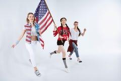 Unga multietniska kvinnor som går med amerikanska flaggan och firar 4th juli Royaltyfri Fotografi