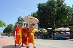 Unga munkar går med paraplyer på gatan i Luang Prabang, Laos Arkivbilder