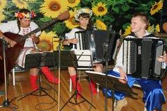 Unga musiker av orkesteren av ukrainska folk instrument som spelar musik i nationella ukrainska dräkter Royaltyfri Foto