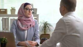 Unga muslim händer för skaka för affärskvinna med en caucasian man under ett möte i regeringsställning arkivfilmer