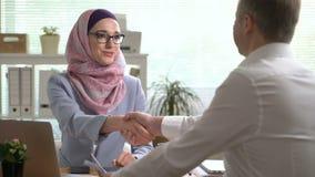 Unga muslim händer för skaka för affärskvinna med en caucasian man under ett möte i regeringsställning stock video