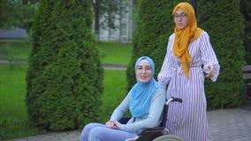Unga muslim inaktiverade i en traditionell halsduk och exponeringsglas i en rullstol som talar till en muslim vän på gatan arkivfilmer