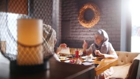 Unga muslim kvinnor som sitter i ett kafé och ett samtal En modern lampa på förgrunden stock video
