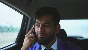 Unga muslim man ridning i en bil i baksätet och samtal på en smartphone stock video