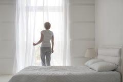 Unga nätta flickaöppningsgardiner i morgonen som får ny luft, baksidasikt royaltyfria foton