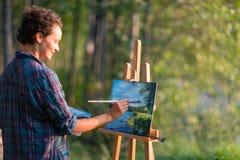 Unga nätta kvinnakonstnärattraktioner målar en bild av en sjö på op royaltyfria foton