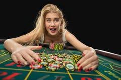 Unga nätta kvinnor som spelar rouletten, segrar på kasinot Royaltyfria Bilder