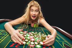 Unga nätta kvinnor som spelar rouletten, segrar på kasinot Royaltyfri Fotografi
