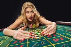 Unga nätta kvinnor som spelar rouletten, segrar på kasinot Arkivfoto