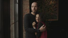 Unga nätta par står nära det panorama- fönstret i kafét arkivfilmer