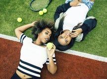Unga n?tta flickv?nner som h?nger p? tennisbanan, danar det stilfulla kl?dda byltet, lyckligt le f?r b?sta v?n tillsammans arkivfoto