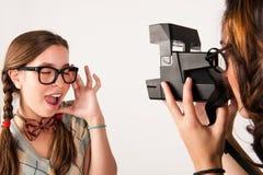 Unga nerdy flickor som använder den ögonblickliga kameran Arkivbilder