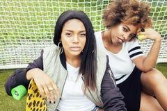 Unga nätta mång- etnicitetafro--amerikan flickor som har gyckel på foothballfältet, fanklubba av byltetonåringar Royaltyfri Bild