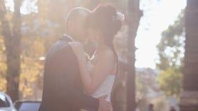 Unga nygift personpar som kysser på höstgatan i Prague den gamla staden arkivfilmer