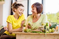 Unga och äldre kvinnor med sund mat inomhus arkivbilder