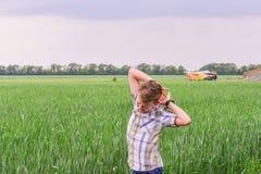 Unga och bekymmerslösa grabbblickar på de gröna öronen av vete, begreppet av framtiden och det nytt royaltyfri fotografi