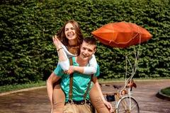 Unga och glade par som har kinkig tillbaka ritt i parkera med Royaltyfri Fotografi