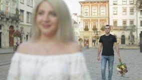 Unga och härliga par i mitten av gatan Man som går till kvinnan med en bukett av blommor långsam rörelse arkivfilmer