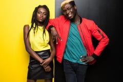 Unga och lyckliga afro amerikanska par som isoleras på färgbakgrund Har den afro amerikanen för mannen och för kvinnan gyckel som royaltyfri foto