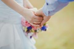 Unga och lyckliga gift parinnehavhänder roman Arkivbild