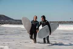 Unga och lyckliga le par av surfare i svarta wetsuits som rymmer sig händer arkivfoto