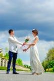 Unga och stiliga nygifta personer på en gå i parkera: ge blommor royaltyfri bild