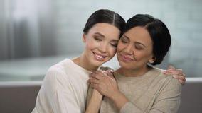 Unga och vuxna kvinnor som omfamnar, nära förhållande av modern och dotter arkivfilmer