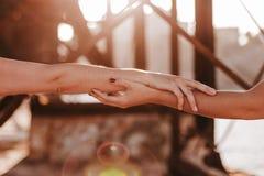 Unga oigenkännliga lesbiska par som utomhus rymmer händer på solnedgången Livsstil och stolthetbegrepp F?r?lskelse ?r f?r?lskelse arkivfoto