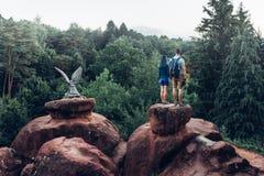 Unga par av fotvandrare som överst står av berget och tycker om sikt av naturen i sommar arkivbilder