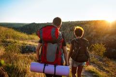 Unga par av handelsresande med ryggsäckar som reser i kanjon på solnedgången royaltyfri foto