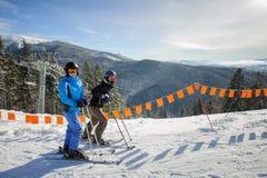Unga par av kvinnor som tycker om som skidar på, skidar semesterorten Royaltyfria Bilder