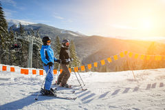 Unga par av kvinnor som tycker om som skidar på, skidar semesterorten Arkivbild