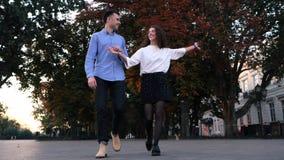 Unga par av mannen och kvinnan som går i höststad Det stilfulla lyckliga paret eller studenter i affär beklär innehavhänder arkivfilmer