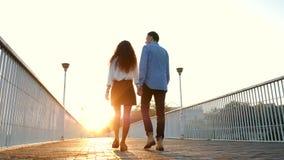 Unga par av mannen och kvinnan som går på bron på sommartid Solnedgången tänder Stilfulla lyckliga par i affärskläder stock video