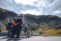 Unga par av motorcykelhandelsresande i höstbergen av Rumänien Moto turism och stund för motohandelsresandelivsstil royaltyfri fotografi