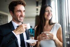 Unga par av professionell som pratar under ett kaffeavbrott royaltyfri bild