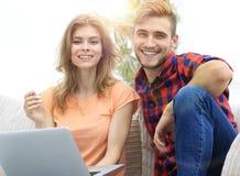 Unga par av studenter med bärbar datorsammanträde på soffan arkivfoto