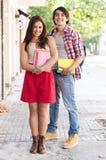 Unga par av studenter som rymmer böcker Arkivbild
